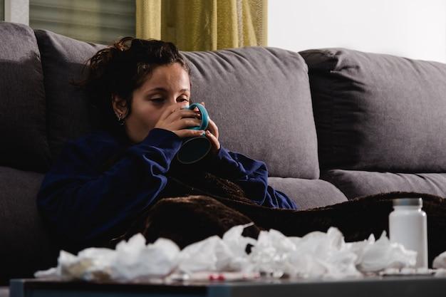 Mulher doente no sofá em casa tomando uma bebida quente