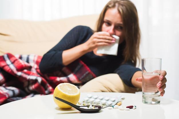 Mulher doente que encontra-se no sofá sob o cobertor de lã que espirra e que limpa o nariz. pego frio
