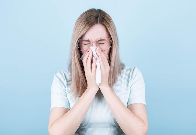 Mulher doente, resfriada, assoa o nariz em um guardanapo
