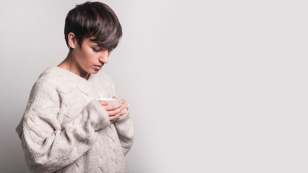 Mulher doente, segurando a xícara de café em pé contra um fundo branco