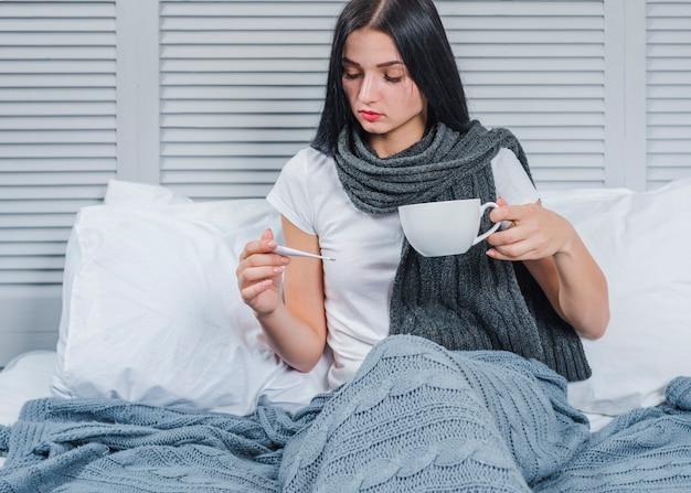 Mulher doente, segurando a xícara de café, olhando para o termômetro