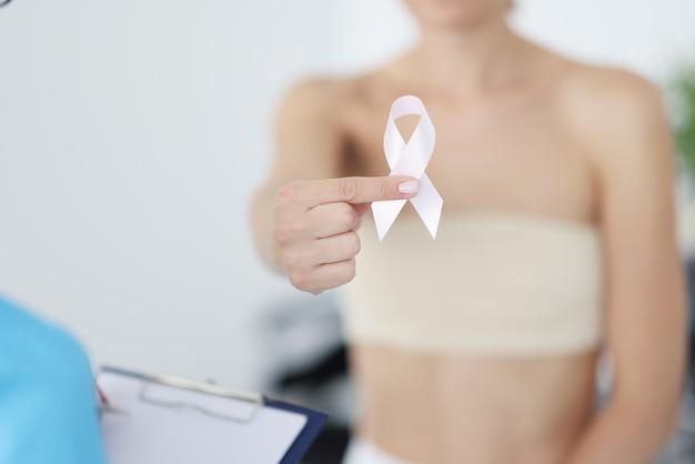 Mulher doente segurando uma fita rosa nas mãos em closeup clínica