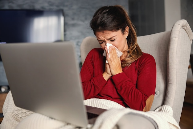 Mulher doente sentada em uma cadeira em casa durante o confinamento com o laptop no colo e assoando o nariz