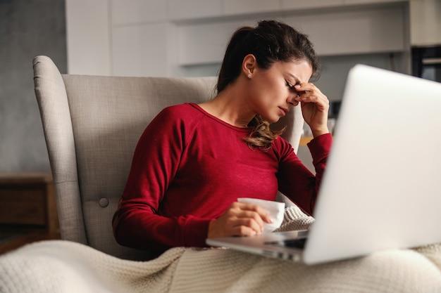 Mulher doente sentada na cadeira em casa durante o bloqueio com o laptop no colo e tendo dor de cabeça.
