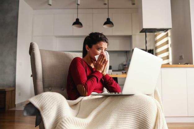Mulher doente sentada na cadeira em casa durante o confinamento com o laptop no colo e assoando o nariz