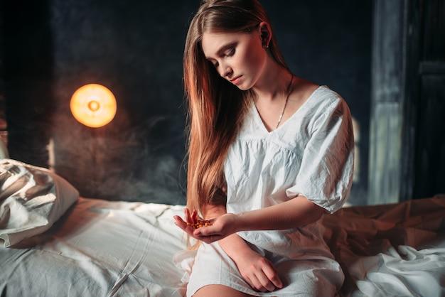 Mulher doente sentada na cama do hospital, drogas nas mãos
