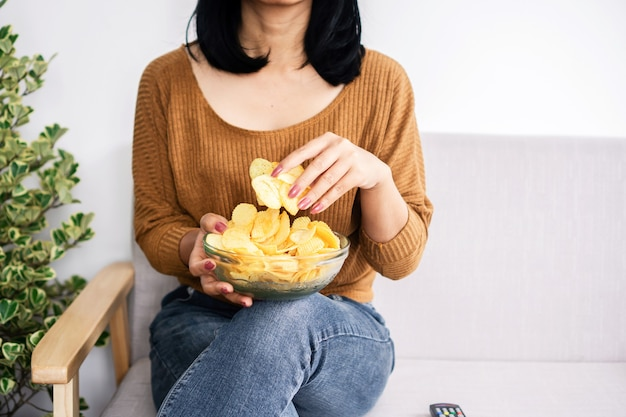 Mulher doente sentada no sofá comendo batata frita na tigela de alguma coisa