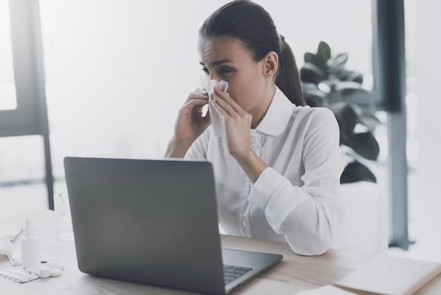 Mulher doente sentado no seu local de trabalho no escritório.