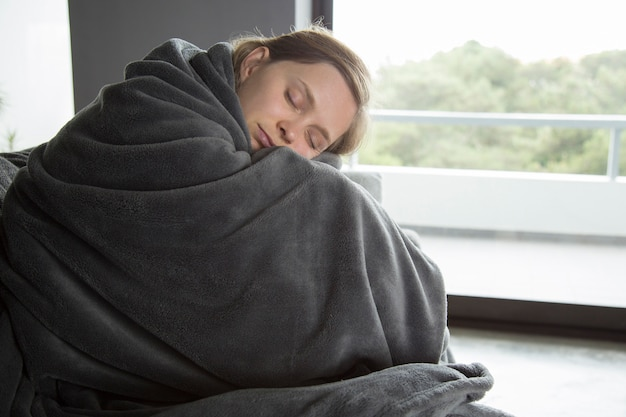 Mulher doente sentado no sofá com os olhos fechados, abraçando os joelhos