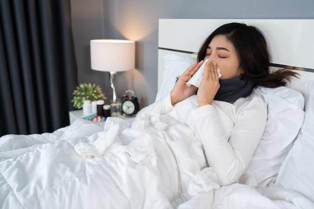 Mulher doente, sentindo frio e espirros na cama
