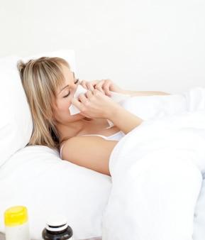 Mulher doente soprando deitada em uma cama