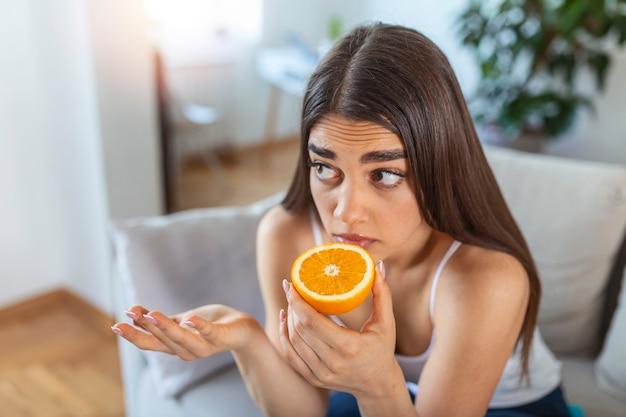 Mulher doente tentando sentir o cheiro de meia laranja fresca, apresenta sintomas de covid-19, infecção pelo vírus corona - perda do olfato e do paladar. um dos principais sinais da doença.