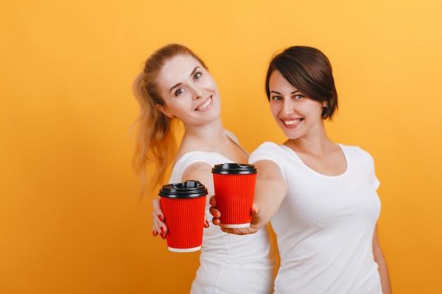Mulher dois feliz que prende um vidro de papel do café nas mãos retas.