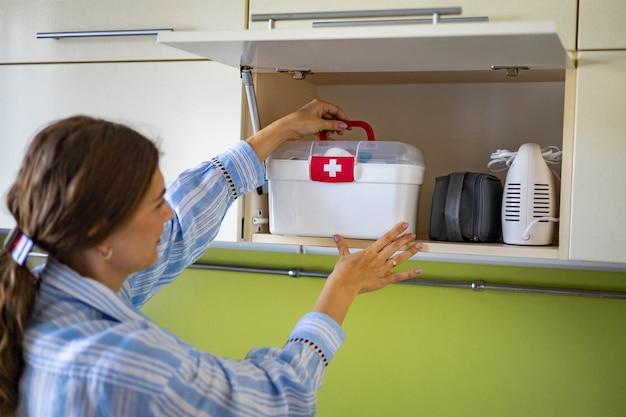 Mulher doméstica colocando kit de primeiros socorros com vitaminas, medicamentos, antibióticos e cura no armário da cozinha
