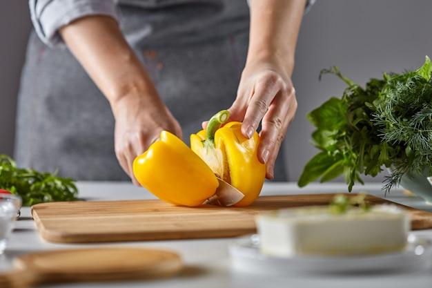 Mulher dona de casa corta pimenta amarela para salada na mesa da cozinha