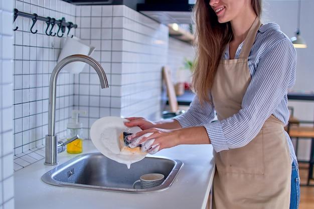 Mulher dona de casa de avental lavando pratos em uma cozinha estilo loft moderno
