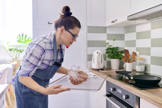 Mulher dona de casa de avental preparando carne de porco na manga de cozimento em casa, coloca a bandeja de carne no forno
