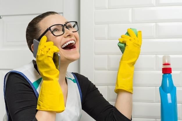 Mulher dona de casa está limpando o banheiro e está sorrindo, falando ao telefone.