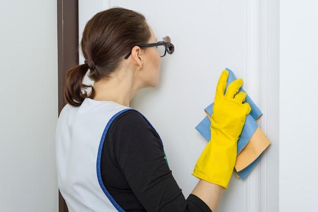 Mulher dona de casa olha no olho mágico da porta da frente no apartamento