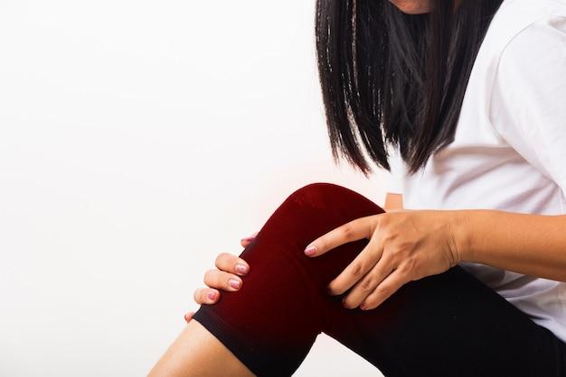 Mulher dor no joelho e ela usa a articulação da mão segurar a agonia do joelho