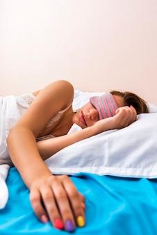 Mulher dormindo com máscara de dormir