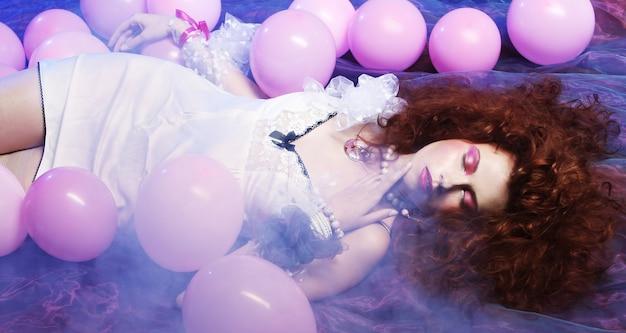 Mulher dormindo deitado no chão entre balões