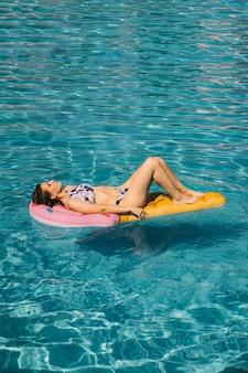 Mulher dormindo em colchão inflável na piscina