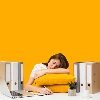 Mulher dormindo em travesseiros em cima de sua mesa