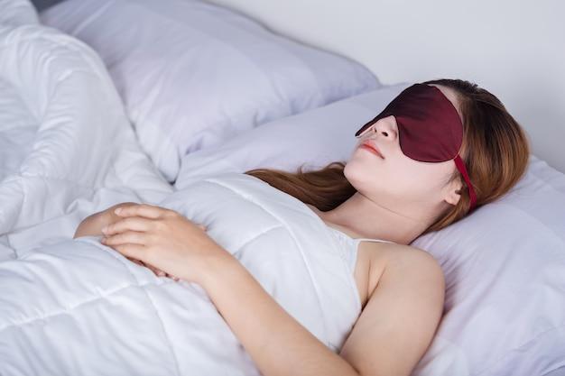 Mulher dormindo na cama com máscara de olho Foto Premium
