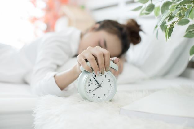 Mulher dormindo na cama enquanto seu alarme mostra a hora de início em casa no quarto