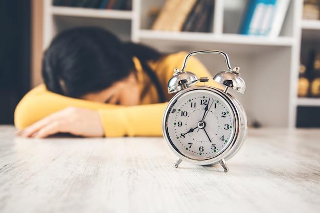 Mulher dormindo na mesa com relógio