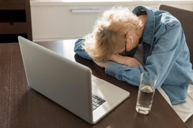 Mulher dormindo na mesa da cozinha perto do laptop