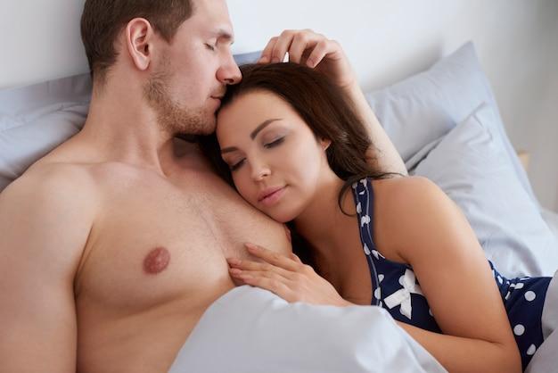 Mulher dormindo nos braços de seu homem