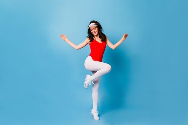 Mulher dos anos 80 salta na parede azul