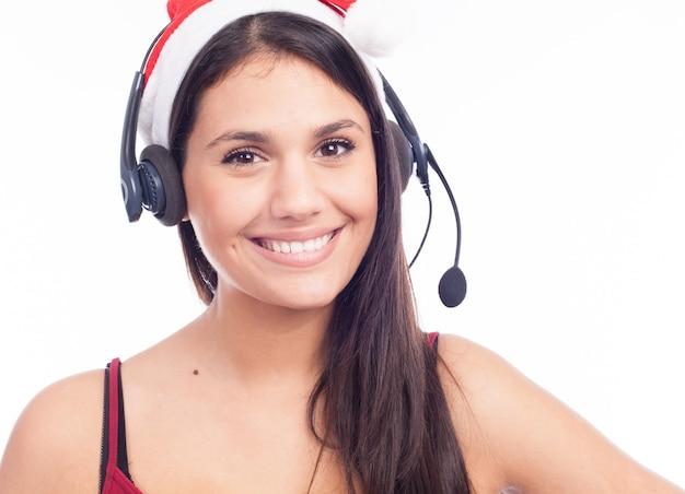 Mulher dos auriculares do natal do centro de atendimento da televenda que veste o sorriso de fala vermelho do chapéu de santa isolado no fundo branco.