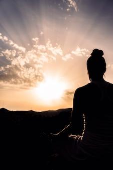 Mulher durante a meditação com o pôr-do-sol
