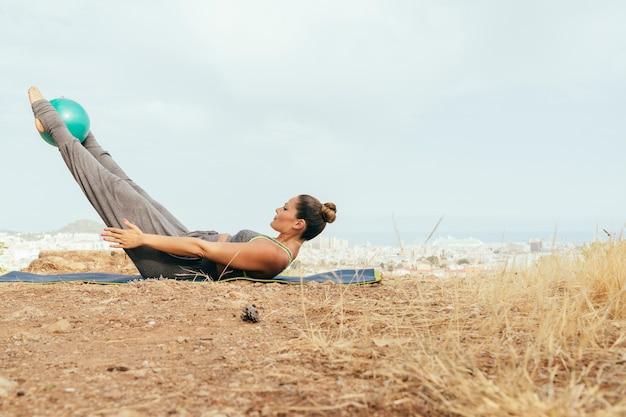 Mulher durante a sessão de yoga difícil ao ar livre