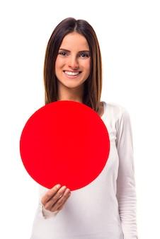 Mulher durante o tratamento segurando placa vermelha redonda para texto.