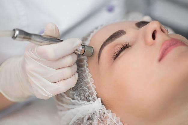 Mulher durante tratamento de microdermoabrasão em salão de beleza