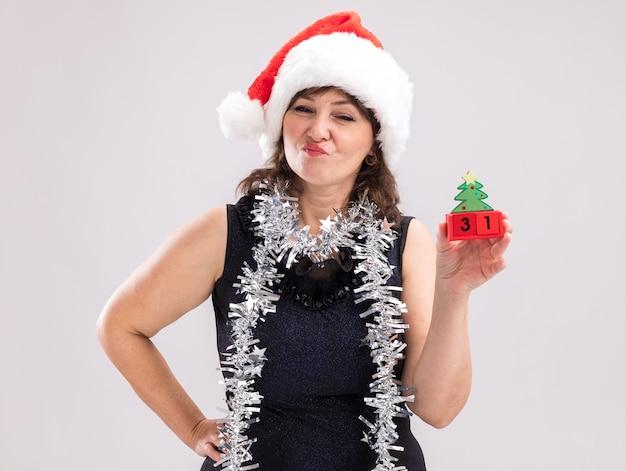 Mulher duvidosa de meia-idade usando chapéu de papai noel e guirlanda de ouropel no pescoço segurando o brinquedo da árvore de natal com data mantendo a mão na cintura, olhando para a câmera isolada no fundo branco