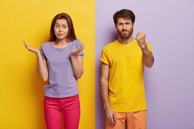 Mulher duvidosa questionada estende as palmas das mãos para os lados, sem expressão facial, homem zangado mostra punho para a câmera