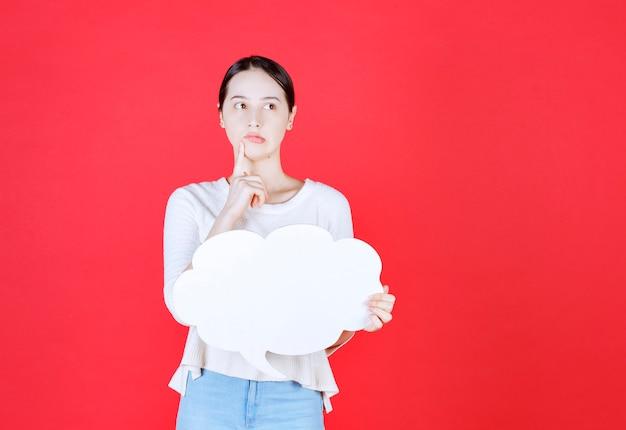 Mulher duvidosa segurando um balão de fala em forma de nuvem e olhando para longe