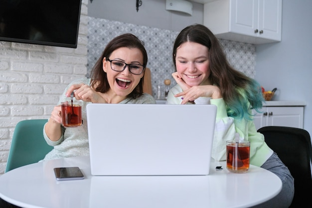 Mulher e adolescente sentados em casa na cozinha, bebendo chá juntos e olhando para o monitor do laptop