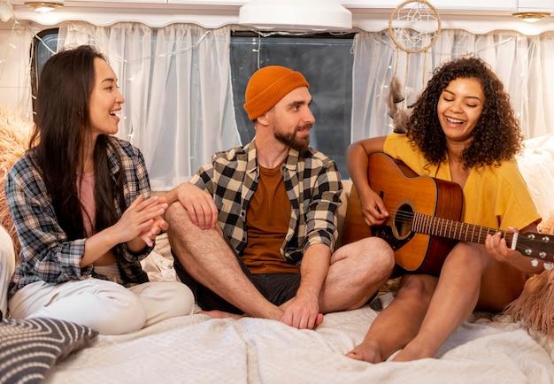 Mulher e amigos tocando violão