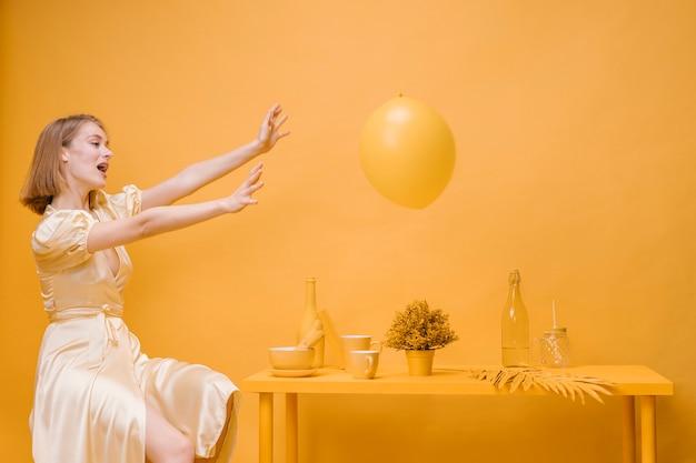 Mulher e balão em uma cena amarela