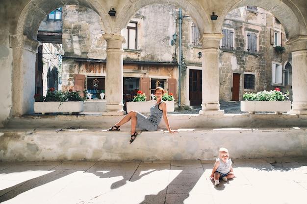 Mulher e bebê na histórica cidade de groznjan croácia mãe com filho na velha rua europeia Foto Premium