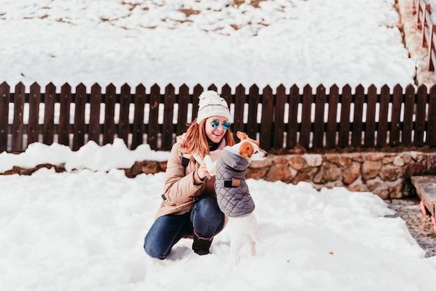 Mulher e bonito jack russell cachorro desfrutando ao ar livre na montanha com neve.