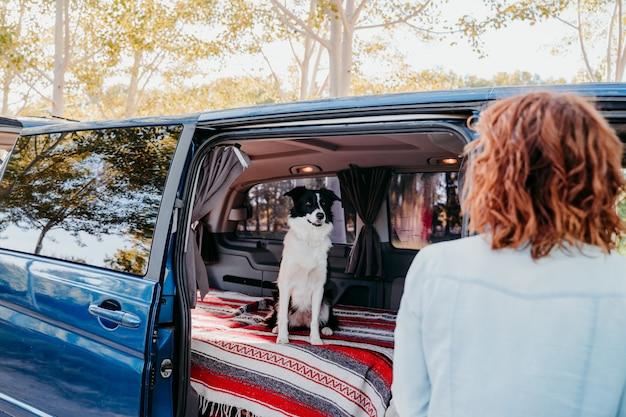 Mulher e cachorro border collie em uma van. conceito de viagens