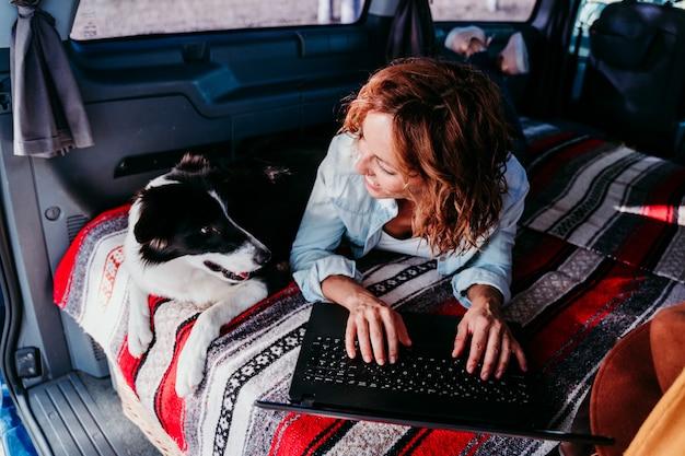 Mulher e cachorro border collie em uma van. mulher trabalhando no laptop. conceito de viagens