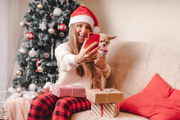 Mulher e cachorro com suéter tirando selfie no natal